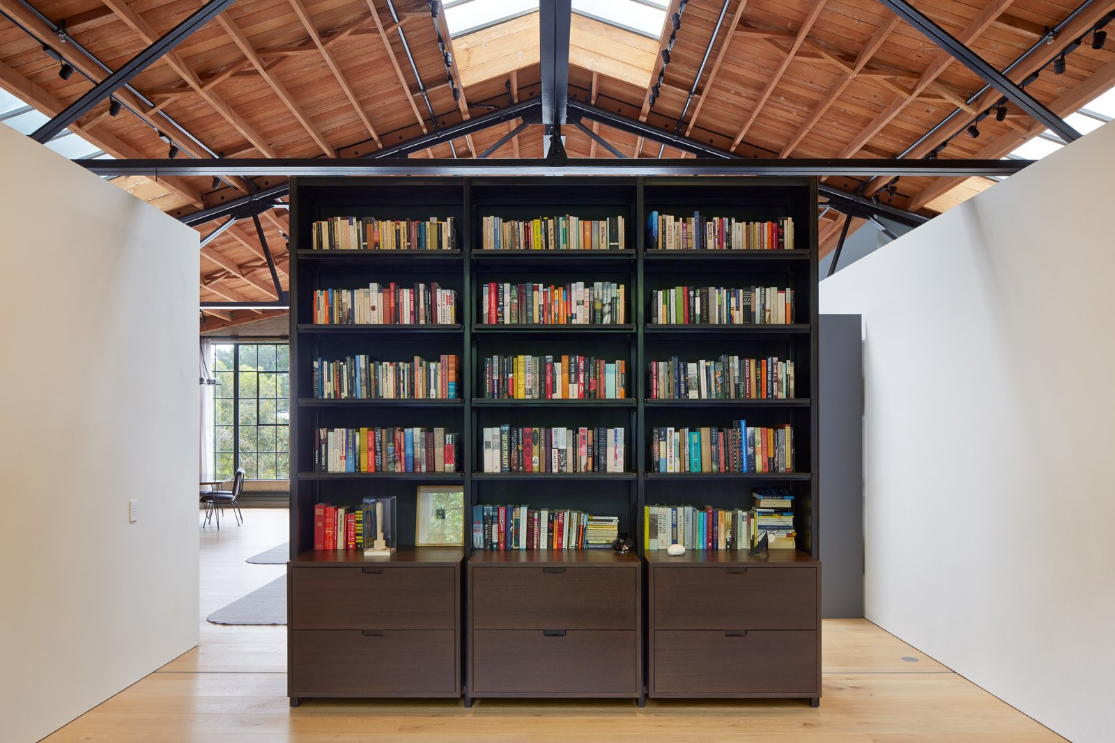 "Fiedler Marciano Architecture crafted not only the loft, but also many of the industrial design objects. The bookcase here is part of the ""black"" family of objects, including the closet storage and stair. The ""white"" family of object include the bathroom, kitchen, and more."