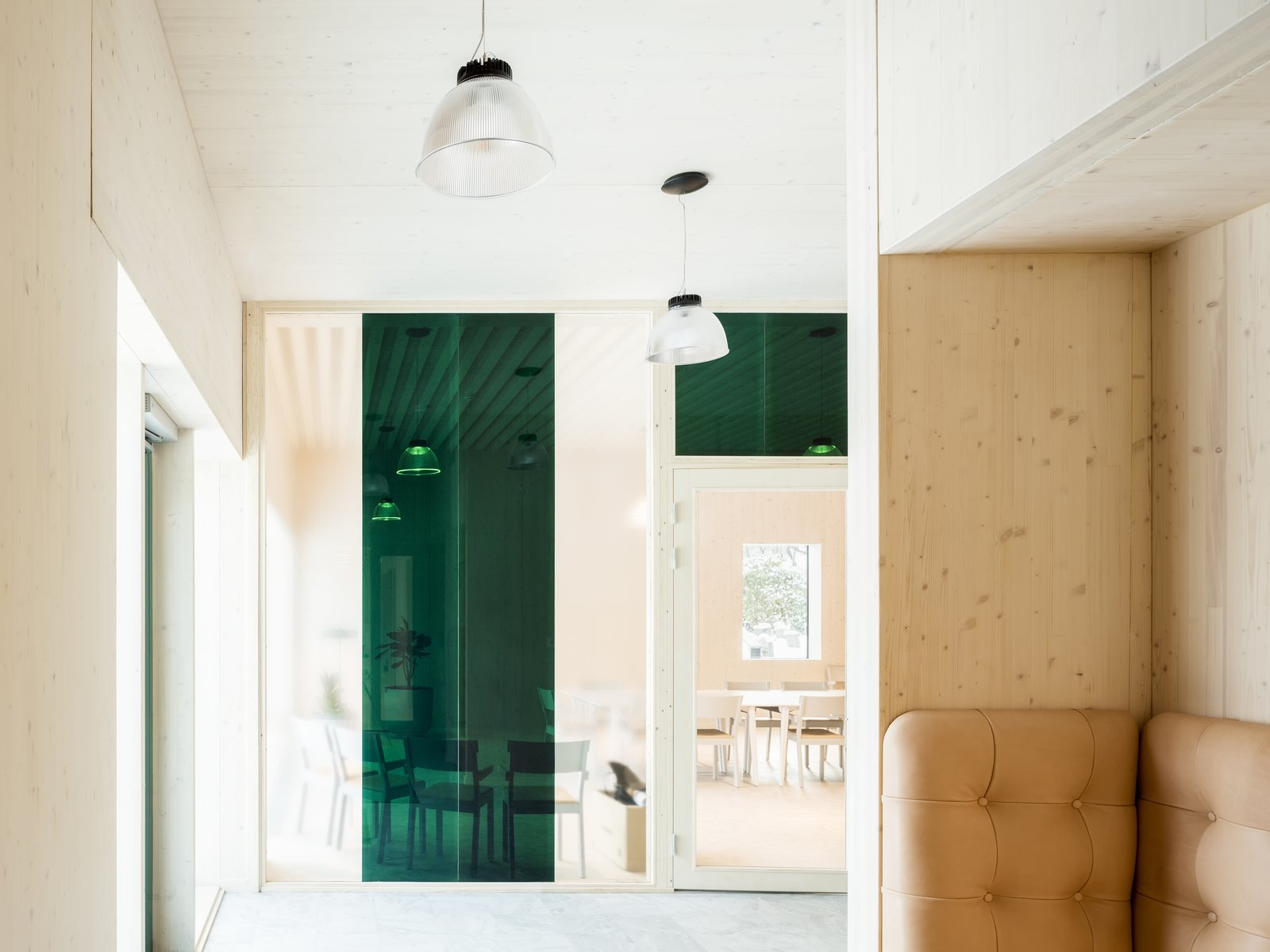 The interior design is characterized by restraint. Wood complements leather and concrete for a modern, natural-looking building that blend together with its lush surroundings.