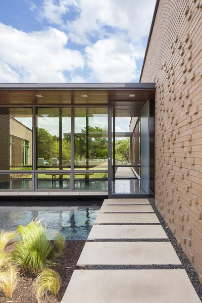 Modern home with casement window type, metal, outdoor, front yard, and pavers patio, porch, deck. Photo 4 of Scout Island Residence - A Masterpiece by alterstudio