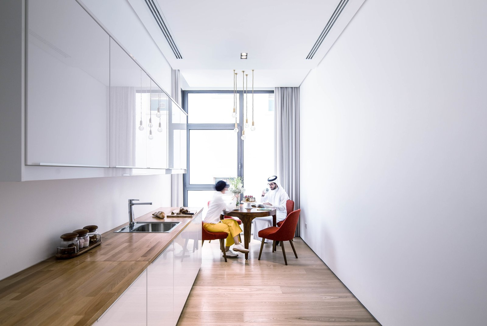 Pantry on the upper floor Tagged: Kitchen, Wood Counter, Ceiling Lighting, Refrigerator, Light Hardwood Floor, Pendant Lighting, White Cabinet, Drop In Sink, Microwave, and Recessed Lighting.  A House in Yarmouk by Studio Toggle