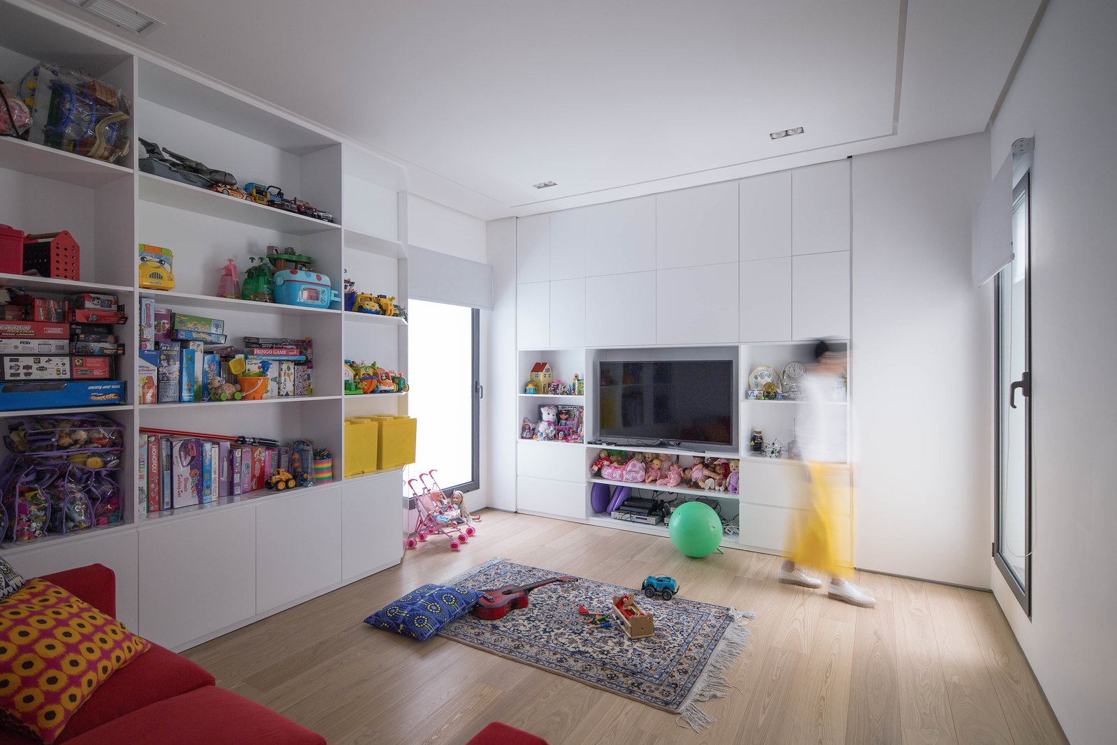 Kids Room Tagged: Kids Room, Bookcase, Storage, Playroom, Light Hardwood Floor, Boy Gender, Girl Gender, and Pre-Teen Age.  A House in Yarmouk by Studio Toggle