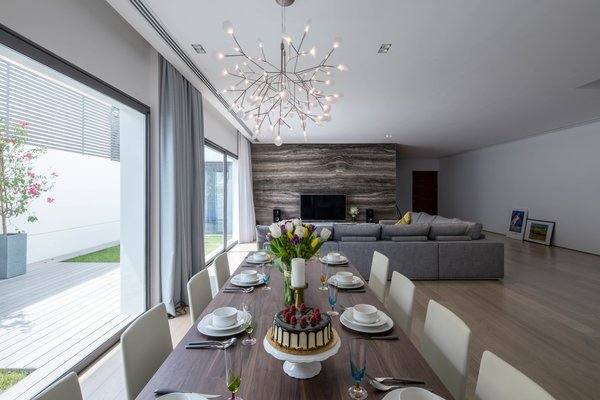 Modern home with dining room, chair, table, light hardwood floor, lamps, ceiling lighting, pendant lighting, and travertine floor. Living room and dining area looking over the private garden Photo 17 of A House in Yarmouk