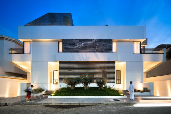 Modern home with outdoor, trees, grass, shrubs, garden, raised planters, front yard, stone patio, porch, deck, concrete patio, porch, deck, metal patio, porch, deck, horizontal fence, metal fence, and landscape lighting. Street view, frontal, dusk Photo 10 of A House in Yarmouk