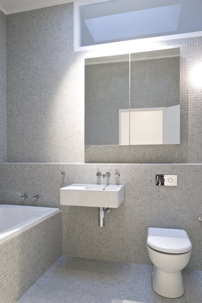 Modern home with bath room, tile counter, wall mount sink, ceiling lighting, glass tile wall, open shower, drop in tub, and one piece toilet. Bathroom Photo 11 of Residence L&N