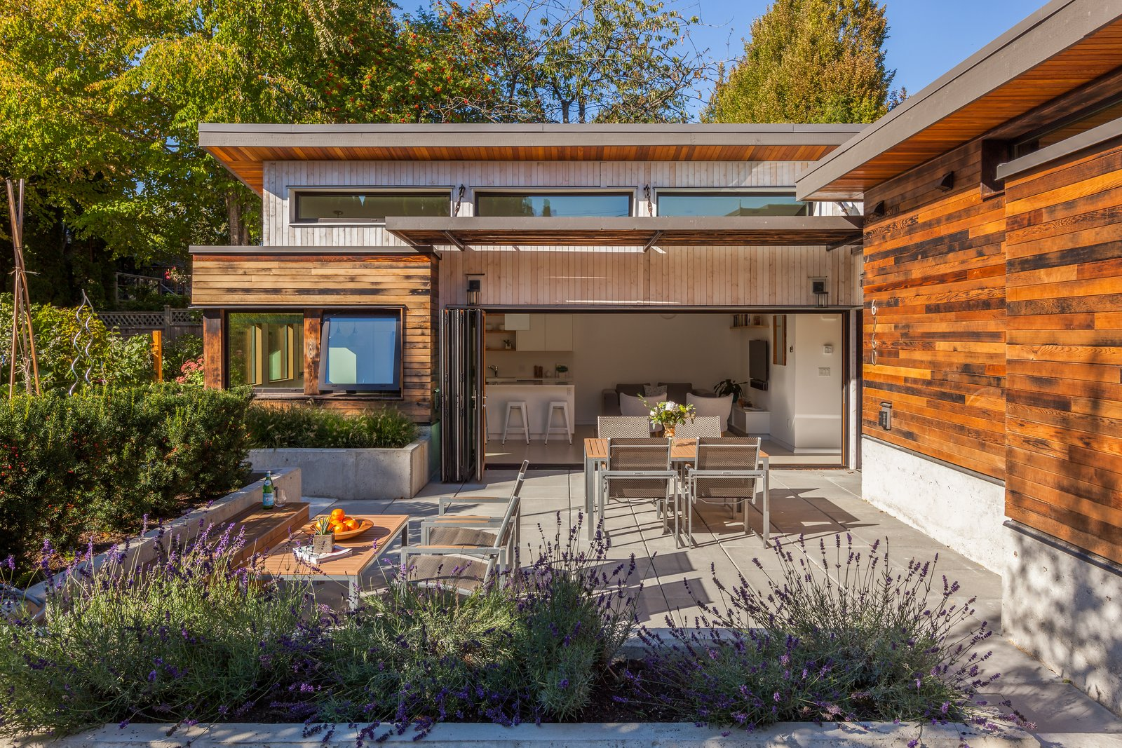 """The lane house sits in the extensive gardens behind the primary residence. Sinking the ground floor 18"""" below grade allows for loftier ceilings while giving the patio a sense of enclosure. 'Two Birds' Infill House by Lanefab Design/Build"""