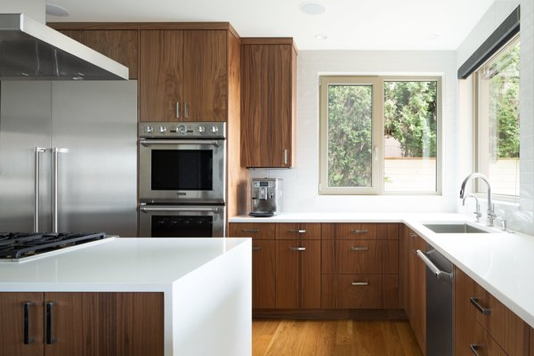 This kitchen boasts an island and a peninsula. Cabinets by Smith and Vallee Woodworks. Photo 5 of The Lakehouse modern home