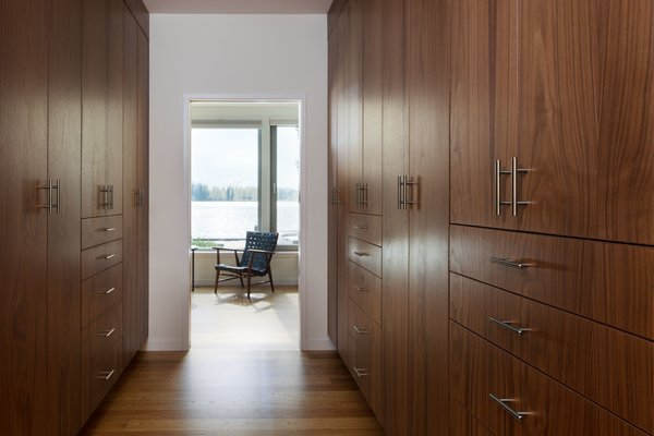 Walk in closet with cabinets by Smith and Vallee Woodworks. Photo 8 of The Lakehouse modern home