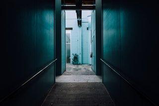 Peering down a dark hallway into cerulean blue green.