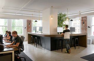 Step Inside Squarespace's Minimalist Portland Office - Photo 3 of 11 - Having large standing spaces in common areas is a newer trend in office spaces, but they allow employees to work in the way that is best suited to them.