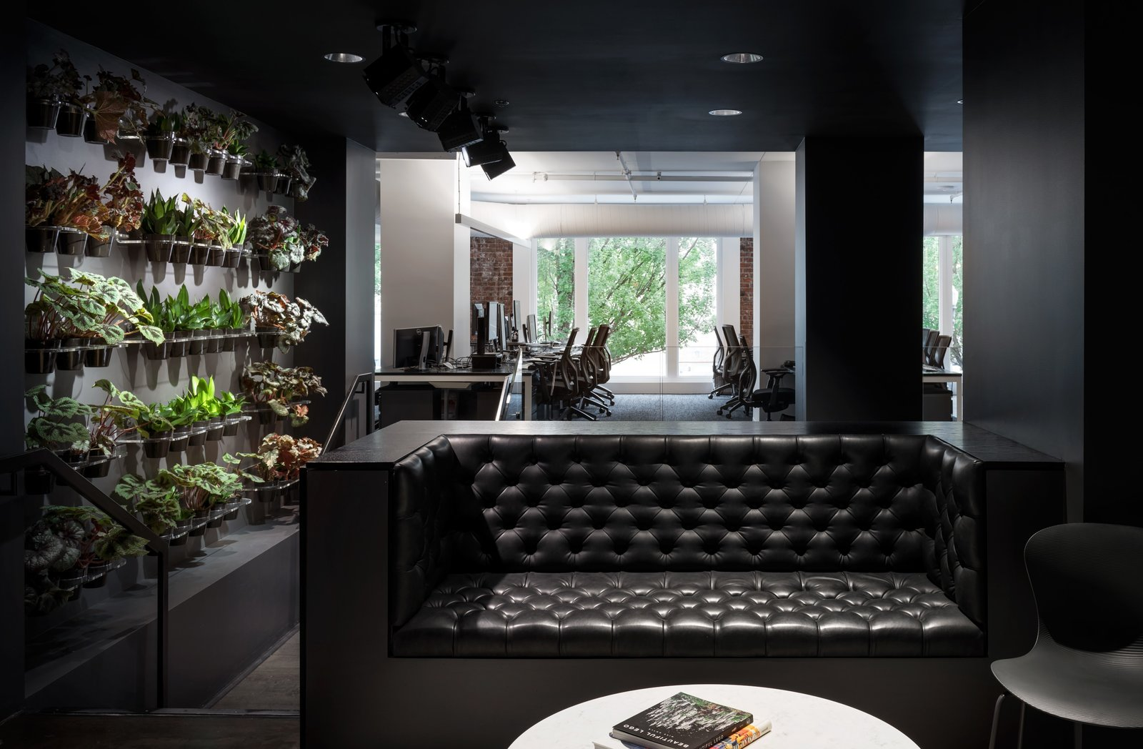 This dark lounge space with dramatic lighting is juxtaposed with a wall of carefully tended plants—hinting at the greenery that Portlanders are surrounded by year round.