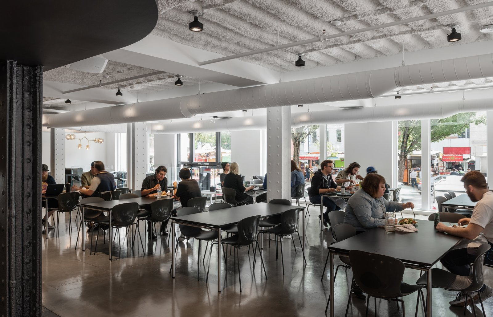 Employees eat at tables in a large entry space with plenty of windows and natural light. Step Inside Squarespace's Minimalist Portland Office - Photo 9 of 12