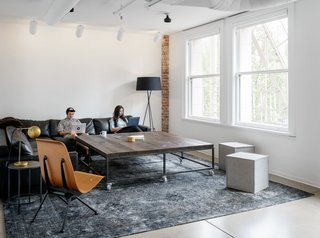 Step Inside Squarespace's Minimalist Portland Office - Photo 10 of 11 - Large tables, modern plywood chairs, and neutral tones offset the white and brick to make a comfortable, open space to work in.