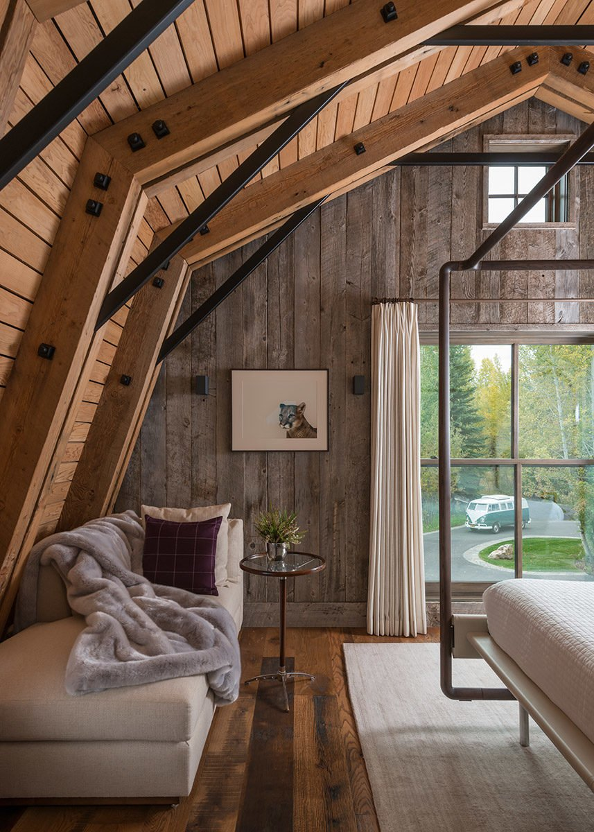 This living/bedroom space showcases neutral tones and shades of white to contrast the continued use of natural, treated wood surfaces.  Photo 3 of 8 in A Guest Barn in Jackson, Wyoming, Fuses Modern and Rustic Elements