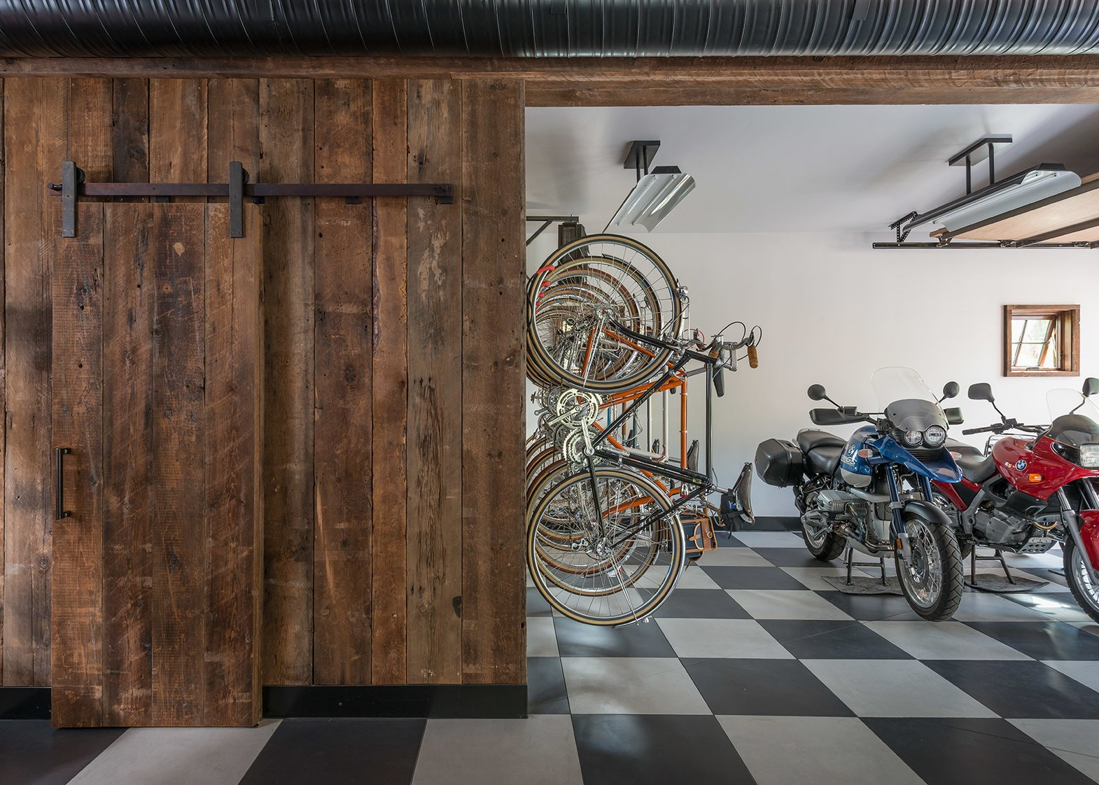 This garage space uses iconic checkerboard floor tiles to contrast the rustic barn door that provides entry to the rest of The Barn. Tagged: Garage and Storage.  Photo 5 of 8 in A Guest Barn in Jackson, Wyoming, Fuses Modern and Rustic Elements