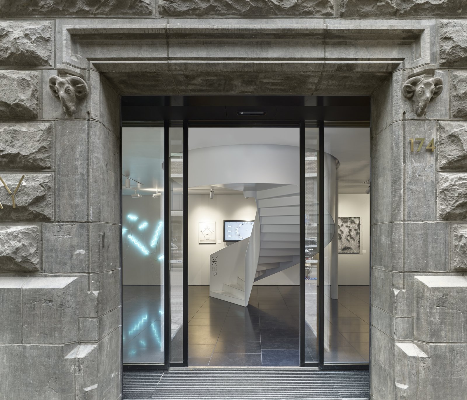 The entrance to X Bank showcases modern works of Dutch art and design which contrast the concrete exterior.  Photo 10 of 14 in Formerly a Historic Bank, This Amsterdam Hotel Honors its Stately Roots