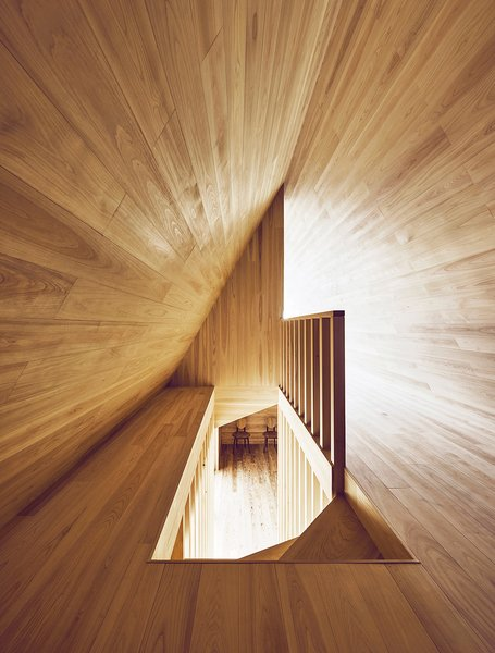 Looking down the stairway from above reveals the A shape of the upper floor and contrasting angles and tones of natural light. Photo 11 of Yoshino Cedar House modern home