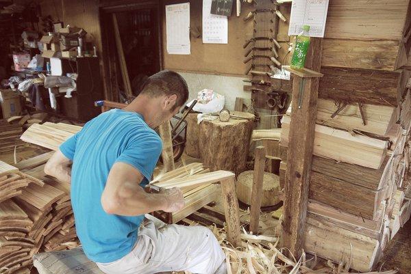 A worker is seen splitting and preparing cedar planks for use in Yoshino Cedar House. Photo 3 of Yoshino Cedar House modern home