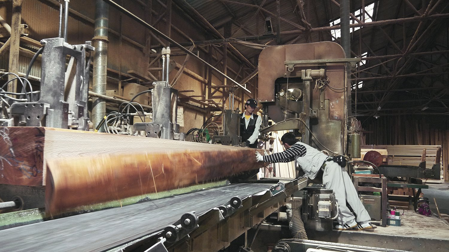 Long beams are prepared by workers in a factory, ready to be used to build Yoshino Cedar House.
