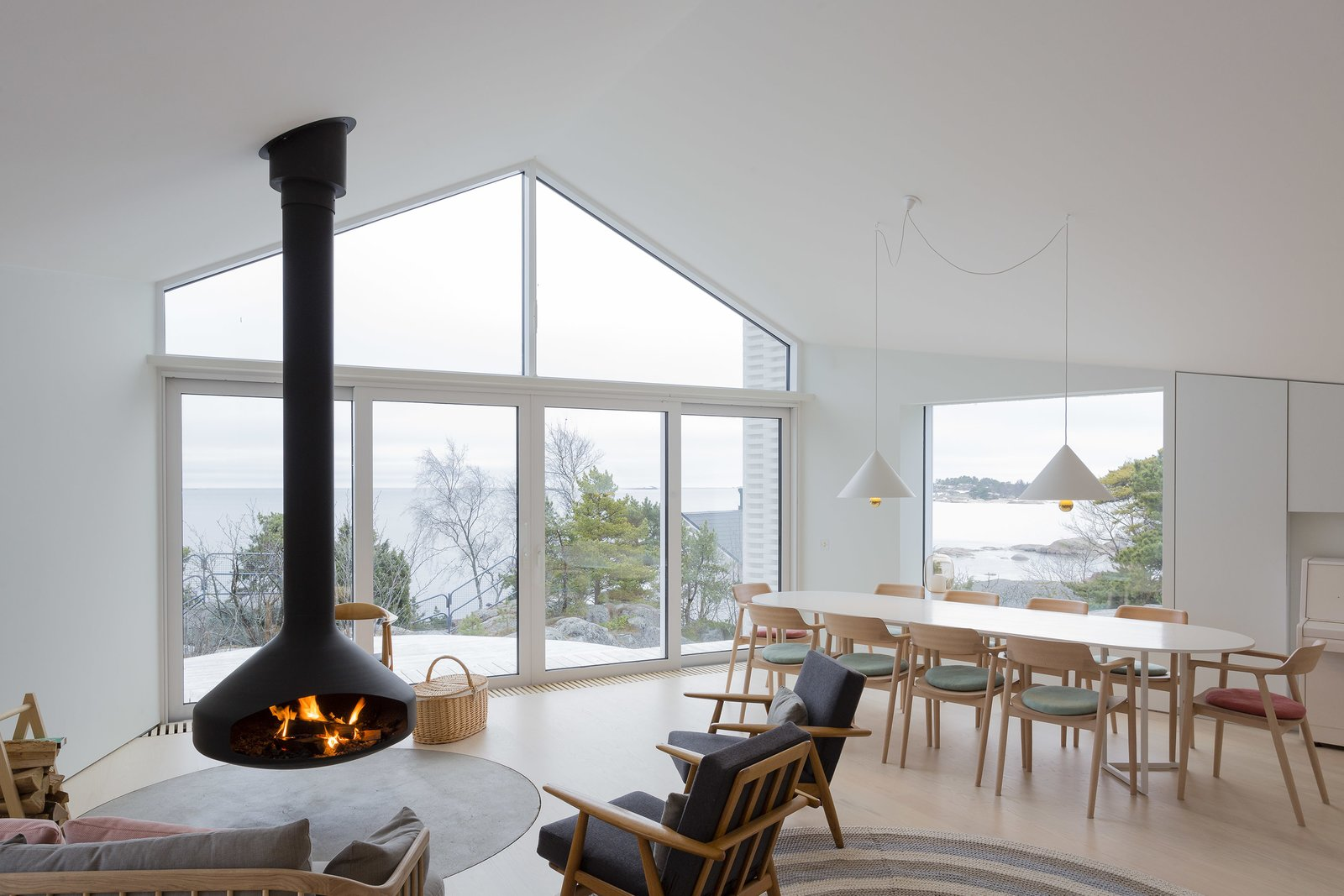 Tagged: Living Room, Light Hardwood Floor, Chair, Hanging Fireplace, Pendant Lighting, and Sofa.  Photo 4 of 12 in A Modern Finnish Villa That Grows Out of a Seaside Cliff