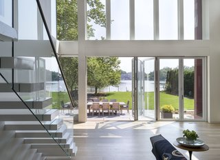 Discover 6 Amazing Riverside Homes - Photo 10 of 12 - The new extension opens out dramatically onto the rear yard, which faces the river. The living space expands beyond indoors and flows outside to an outdoor deck with a large dining table.