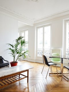 Old-World Charm Meets Modern Finishes in These 6 Parisian Apartments - Photo 7 of 12 - In the 11th arrondissement, the elegance of wood chevron floors, delicate crown molding, and ceiling medallions is balanced by stark white walls and ceilings and a select few pieces of furniture, allowing the white French doors and views to the outside to take priority.