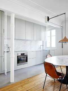 Old-World Charm Meets Modern Finishes in These 6 Parisian Apartments - Photo 8 of 12 - The white walls, ceilings, and decorative crown moldings continue into the kitchen area, where light gray cabinets and a medium gray floor covering highlight the marble of the tabletop and backsplash.
