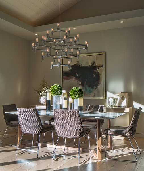 Seductive lighting creates ambiance around a Formworks marble-topped dining table. McGuire dining chairs are comfortable enough to spend an entire evening. Photo 3 of A New Beginning modern home