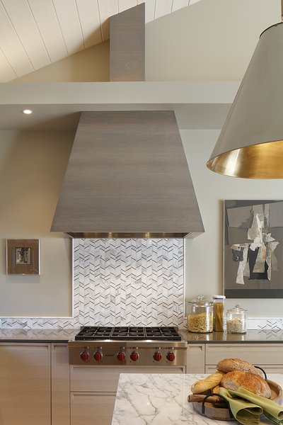 Stove hood is an iconic shape, done in horizontal grain oak stained dark.  Marble mosaic tile over a Wolf range top. Photo 10 of A New Beginning modern home
