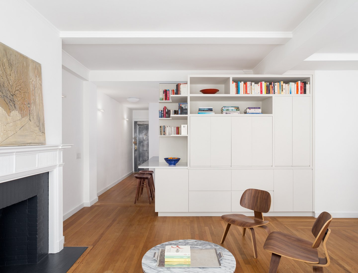 Built in custom millwork conceals the entertainment center and connects to the adjacent kitchen cabinets and counter top.    Prewar Modern Upgrade by kane architecture and urban design