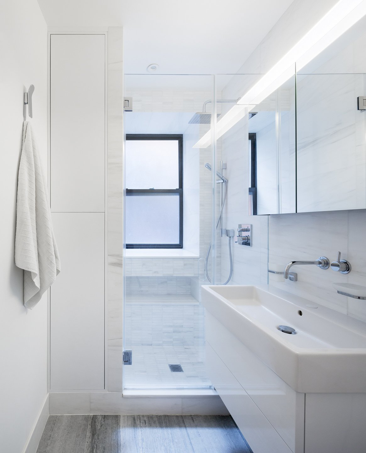A wall mounted vanity,  glass enclosed shower and built in cabinets seek to maximizes the feeling of space within a very tight footprint.