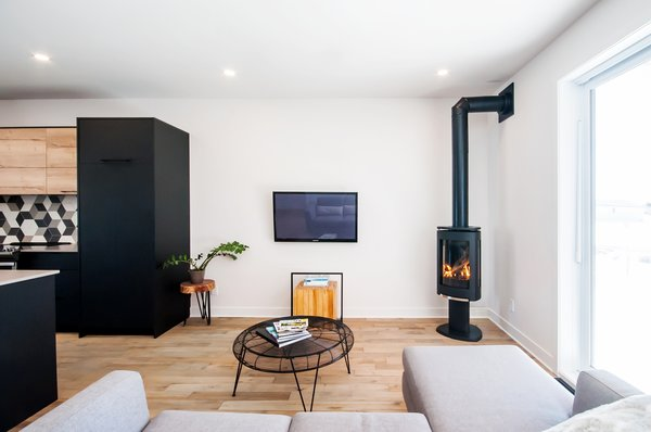 Living room with JOTUL fireplace and FSC oiled maple floors Photo  of Concept DUB House modern home