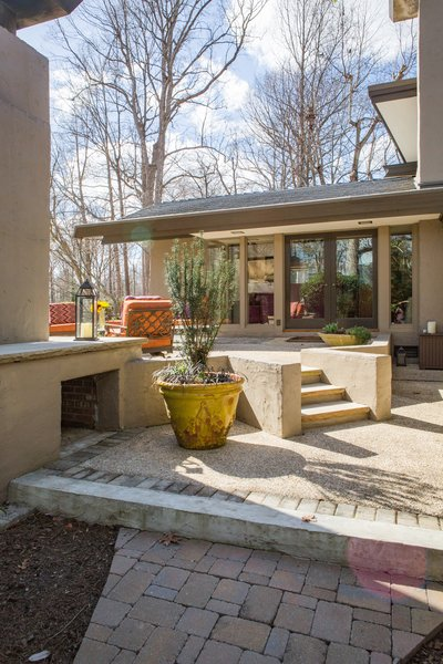 At the end of the paved path, the entrance to the new outdoor gathering space unfolds. Photo 6 of Mid-century Modern Gathering Space modern home
