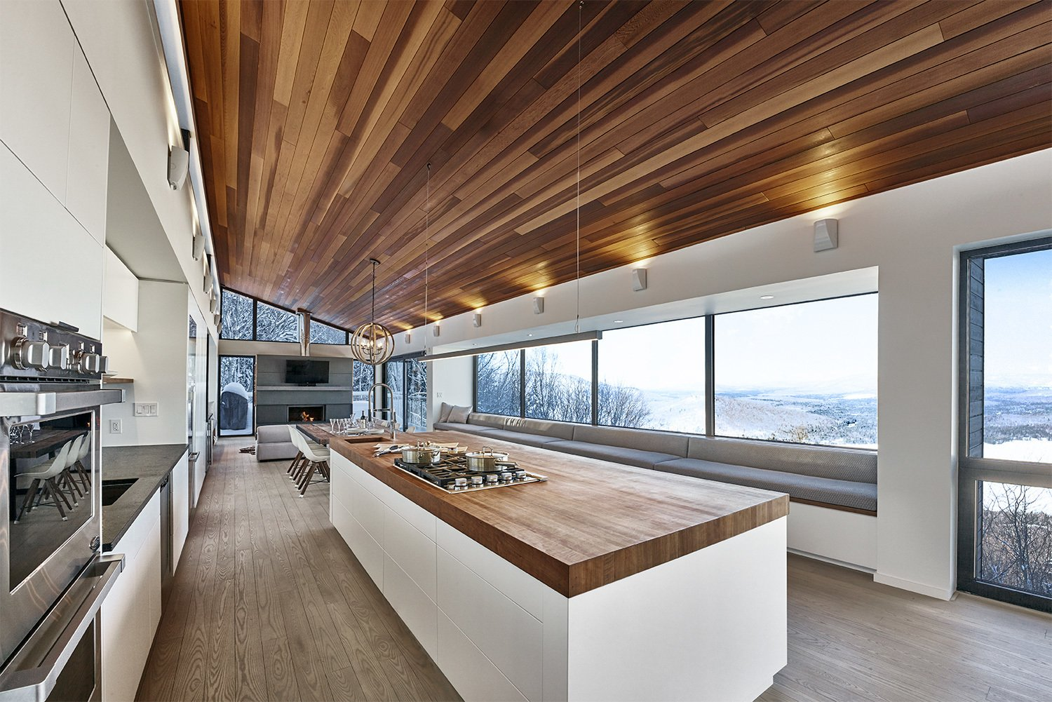 View of kitchen and main bay window upon entry into primary living space.  Laurentian Ski Chalet by RobitailleCurtis