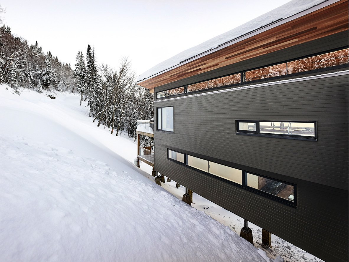 Partial view of main facade from entry bridge. Tagged: Exterior, Wood Siding Material, Metal Roof Material, Shed RoofLine, Cabin Building Type, and House.  Laurentian Ski Chalet by RobitailleCurtis