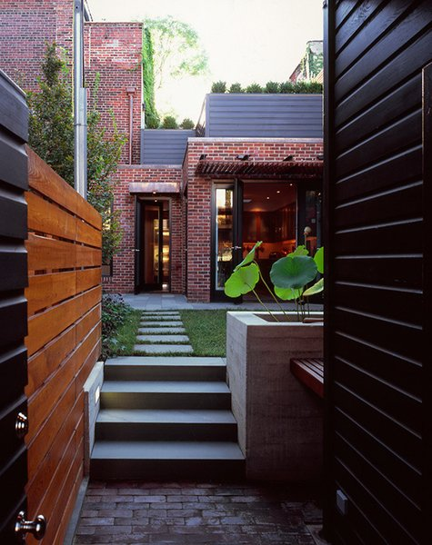 At the threshold between the public realm and the private.  This image is taken at the point of entry to the garden, adjacent the garden shed and driveway that it conceals.  In view are the brick pavers, cedar fence, bluestone treads, board form concrete water feature, and the new kitchen addition with roofdeck beyond.  By RobitailleCurtis Photo 3 of Fitler Square House & Garden modern home