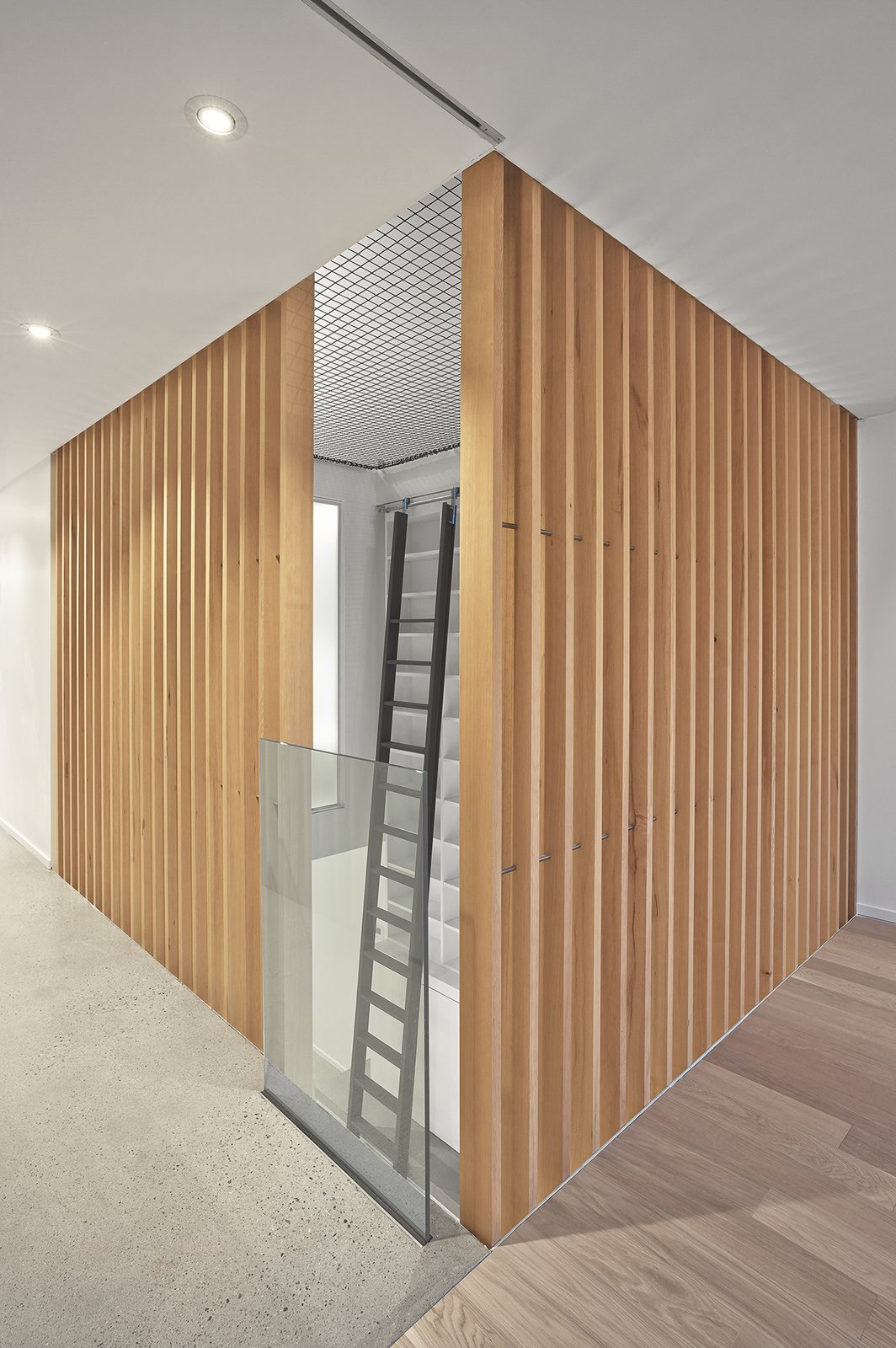 The atrium is 'enclosed' at the second floor level by vertical grain douglas fir slats.  The trapeze net play surface on the third floor can be seen.  Atrium Townhome by RobitailleCurtis