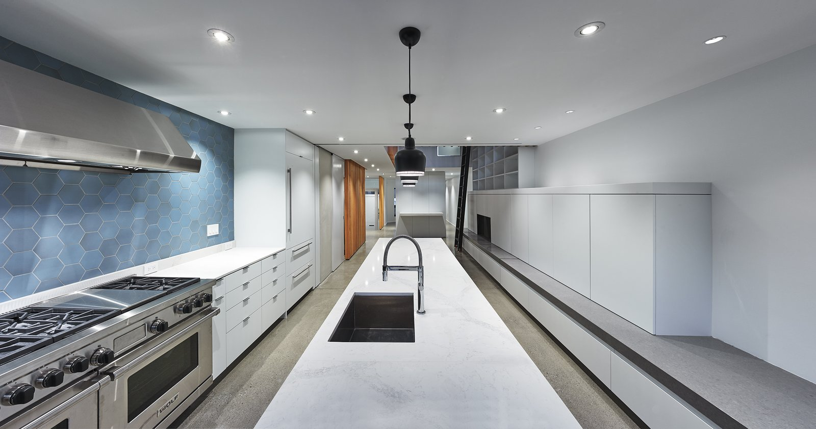 Alvar Aalto's A330 pendant fixtures above the kitchen island. Tagged: Kitchen, White Cabinet, Concrete Floor, Ceramic Tile Backsplashe, Pendant Lighting, Recessed Lighting, Range Hood, Range, Undermount Sink, and Marble Counter.  Atrium Townhome by RobitailleCurtis