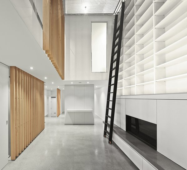 View of the main atrium space with vertical grain douglas fir wood slats, and custom steel library ladder.