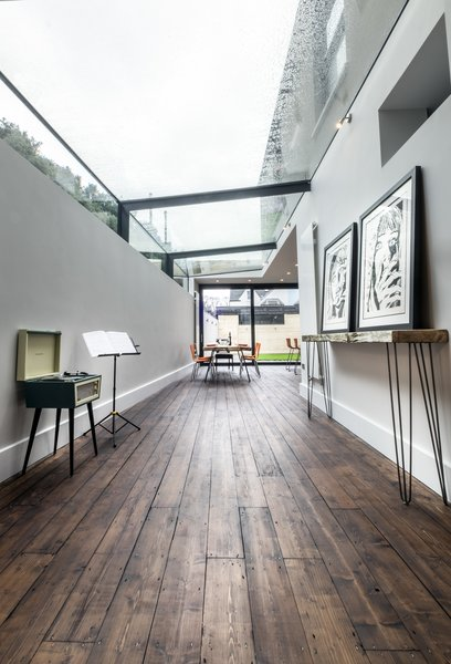 Modern home with dining room, chair, table, ceiling lighting, and dark hardwood floor. The glass panels had to be made in Germany and craned into place Photo 3 of THE GLASSHOUSE