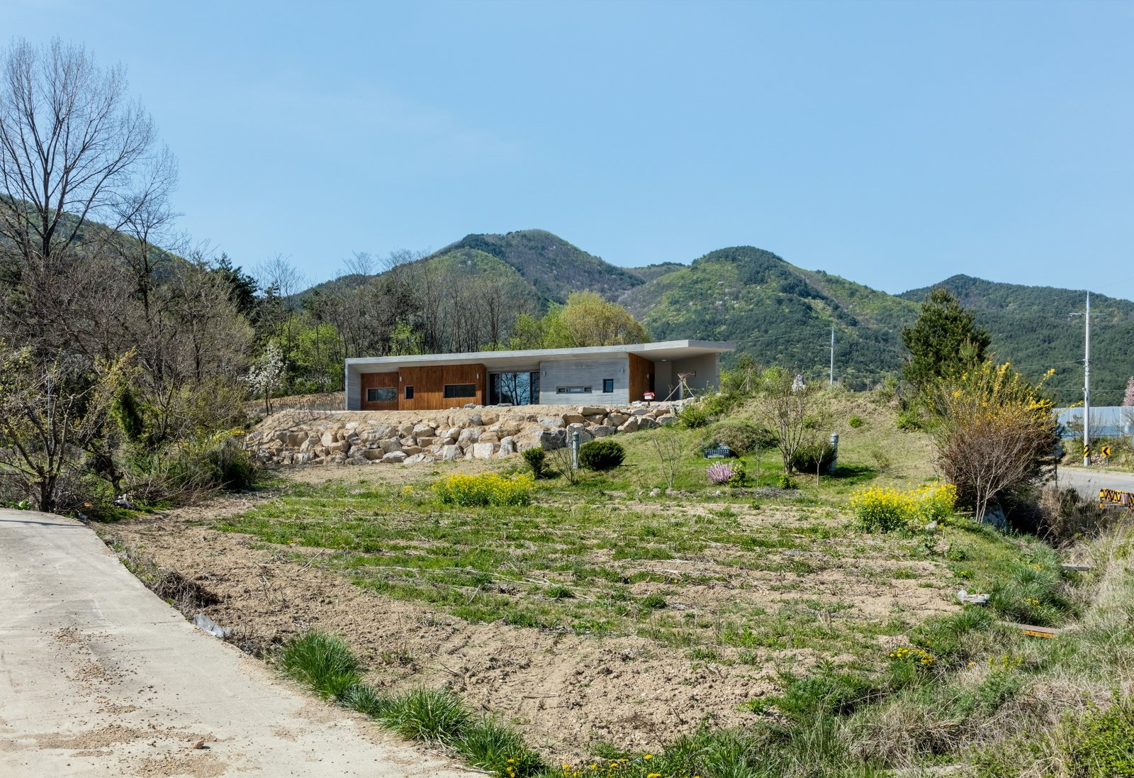 distant view Tagged: Outdoor, Front Yard, Trees, Grass, and Flowers. Apple Farm House by 2m2 architects