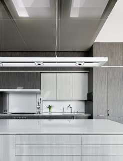 Making Space - Photo 3 of 3 - An overhead lighting fixture by ALW hangs above the island's gray/white stained engineered oak, which contrasts with the cabinet's darker gray engineered oak.