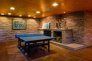 What Would Victor Do? - Photo 4 of 11 - The rumpus room delighted the Kohn<br>family, with its sprawling fireplace,<br>television seating, and honed-flagstone<br>arena for ping pong—a sport the<br>current owners of One Eudora also<br>enjoy. The articulated wood figures<br>on the mantel, made for a gym in the<br>early 20th century, were used to teach<br>children how to box. The framed vellum<br>is a historic Denver-area trolley sign.