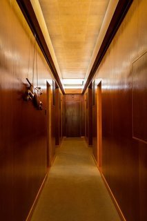 What Would Victor Do? - Photo 5 of 11 - A long clerestory illuminates the hallway dividing the bedroom<br>wing of the house. The door at the end originally opened to racquet storage and<br>pathway access to a subterranean tennis court. The carved greyhound dates to<br>the 1920s.