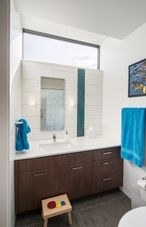 """A light-enhancing transom window in the kids' bathroom mimics the high-floating windows in the adjacent bedroom. Large-scale gray floor tiles and sleek cabinetry contrast with the playful vertical stripe in the tile (""""the owners wanted a little bit of color and pop,"""" says Goff); the hue mimics a teal blue seen throughout the home. Remove the children's stool, and the bath will become sophisticated enough for a teen—or beyond."""
