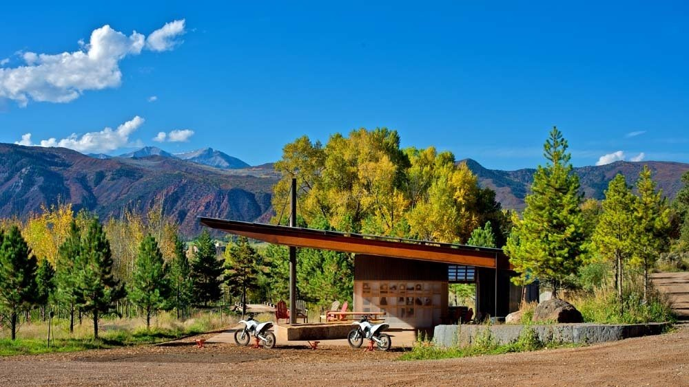 Black Shack Architects designed a modern motocross shelter in an elemental way. When Glenn Rappaport's long-time client approached him to design a shade structure along a private motocross track in El Jebel, Colorado, he was inspired by the elemental nature of the project. The family, with three teenage boys, wanted a shelter that would provide protection from the elements, a small changing area, restroom, fire pit, and storage for cold drinks.