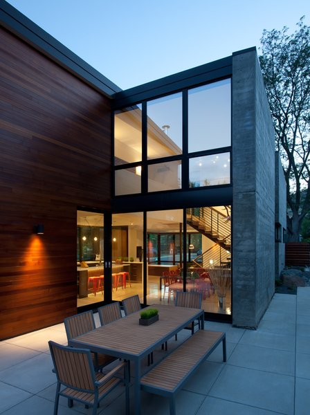 "The back patio becomes another dining room when a full wall of doors open from the kitchen/dining area. In warm months, the couples' young son pushes his Strider Bike between the spaces. ""He could do laps around the whole house if he wanted to,"" said his dad. Cedar siding brings warmth to the concrete patio and board-formed, concrete accent wall."