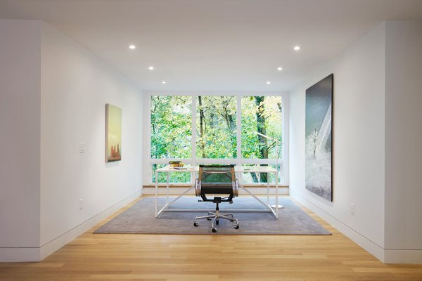 Situated on a sloped-site, each renovated space provides a unique perspective and vista to the dramatic natural surroundings. The office, with its stark modern furnishings and subtle artwork, allows the large window to serve as perhaps the most dramatic, singular frame to the foliage beyond. Photo 9 of Modern Victorian modern home