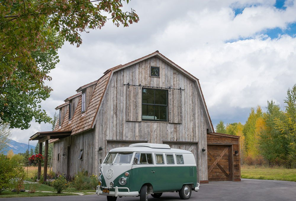 """THE BARN – What looks from the exterior like a possible renovation project was actually built from the ground up to resemble the traditional barn form, while also incorporating modern and contemporary elements. Said Eric Logan, """"In keeping with the rest of the architecture of the compound of buildings there, this needed to be a traditional take on architecture, with the old wood, the gambrel roof form, and the dormers."""" The interior expression, on the other hand, is light and airy, with an exposed structural system and floor-to-ceiling glass walls on the upper level. """"You ascend the stairway and get this beautiful view of the structure and the contrast of light and dark in the ceiling. Then there's this incredible exposure from 15 feet off the deck, and the dramatic view of the Teton range beyond."""" Photos by Audrey Hall. Guide to 7 Main Types of Roofs and What You Need to Know About Them - Photo 5 of 16"""