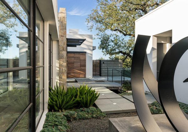 Modern home with outdoor, hardscapes, walkways, shrubs, landscape lighting, and side yard. Sculpture courtyard and lighted pathway Photo 3 of Hilltop Haven