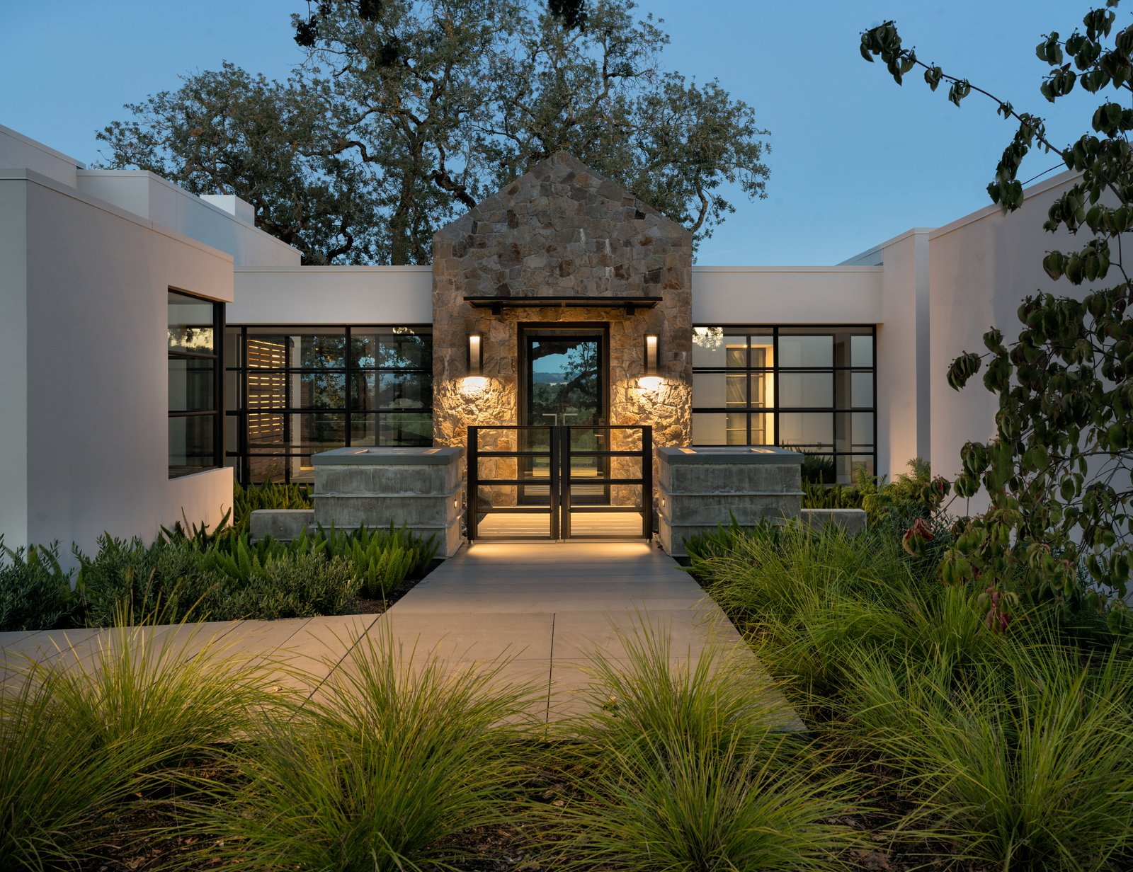 A warmly welcoming entrance to the home Tagged: Outdoor, Trees, Grass, Shrubs, Landscape Lighting, Concrete Patio, Porch, Deck, Hardscapes, Back Yard, and Garden. Hilltop Haven by Randy Thueme Design